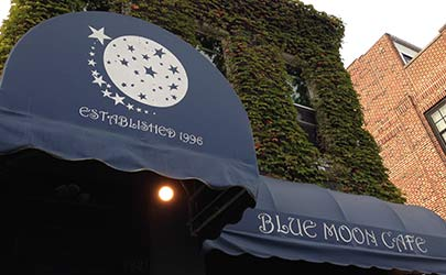 A deep blue storefront awning with branding for the Blue Moon Cafe in Fells Point, Baltimore