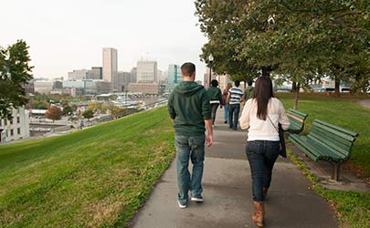 A group of students walking down a sidewalk on a hill with the Baltimore skyline in the background