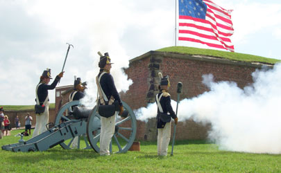 A cannon surrounded by reenactors dressed in military uniforms fires at Fort McHenry in Baltimore
