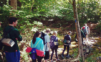 A group of people hiking down a trail in a wooded area of Gunpowder Falls State Park