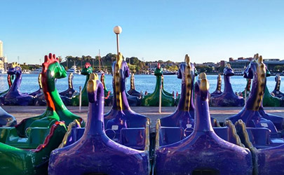 Rows of paddle boats shaped like dragons overlook the Inner Harbor of downtown Baltimore