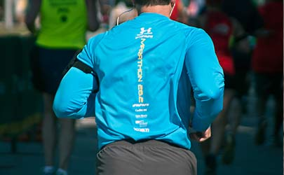 The backside of a person in running clothes running in a marathon