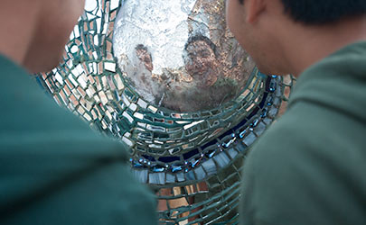 A pair of people looking at their reflection on a piece of art created from a mosaic of glass