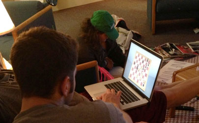A student plays chess on their laptop in a dorm room