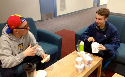 Two students eating Chinese food in a common area of their dorm