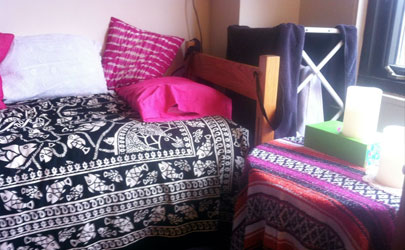 A tidy, decorated bed set and side table in a dorm room