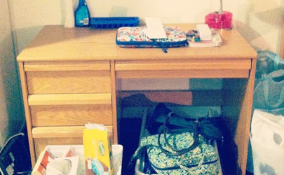A side table with a laptop case and other items next to a dorm bed