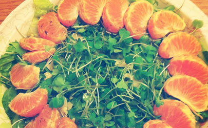A ring of orange slices encircles a plate of leafy greens