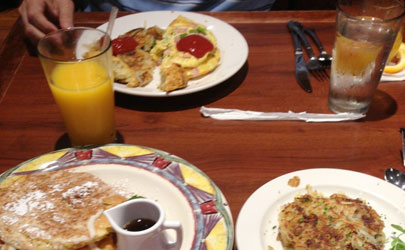 A breakfast of pancakes, omelettes, and hash browns on a dining table