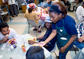 A student serving meals to people seated at a table